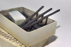 Естественные ручки угля и пакостный ластик в старой картонной коробке Стоковое Изображение RF