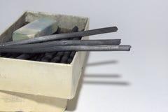 Естественные ручки угля и пакостный ластик в старой картонной коробке Стоковое фото RF