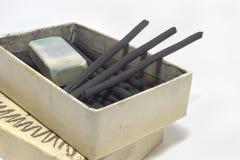 Естественные ручки угля и пакостный ластик в старой картонной коробке Стоковые Фото