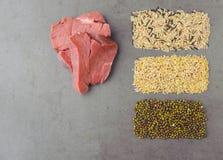 Естественные сырцовые ингридиенты для корма для домашних животных на серой предпосылке Стоковые Изображения
