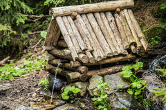 Естественный источник ключевой воды в лесе пропуская от деревянного колодца Стоковая Фотография RF