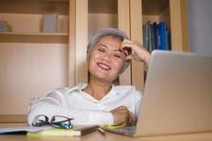 Естественный портрет офиса образа жизни привлекательной и счастливой успешной зрелой азиатской женщины работая на усмехаться стол стоковое фото rf