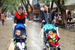 2 детеныша будут матерью нажатия прогулочной коляски в пешеходной улице Стоковые Изображения RF