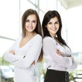 2 детеныша, оружия привлекательной успешной бизнес-леди стоящие пересекли dyadom Стоковые Фотографии RF