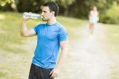 детеныши воды человека бутылки выпивая Стоковые Фото