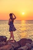 детеныши женщины захода солнца наблюдая Стоковые Фотографии RF