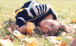 детеныши женщины листьев осени лежа Стоковые Фото