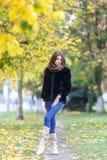 детеныши женщины красивейшего парка осени гуляя Концепция fashin осени Стоковая Фотография
