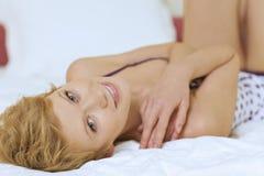детеныши женщины кровати лежа Стоковые Фотографии RF