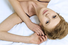 детеныши женщины кровати лежа Стоковые Изображения RF
