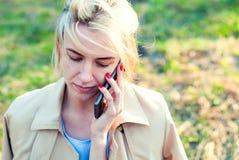 детеныши женщины мобильного телефона говоря Красивая белокурая девушка с мобильным телефоном на солнечный день Стоковое Изображение