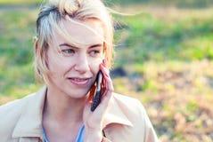 детеныши женщины мобильного телефона говоря Красивая белокурая девушка с мобильным телефоном на солнечный день Стоковые Фото