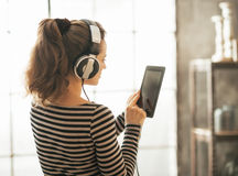 детеныши женщины нот наушников слушая Стоковое Изображение RF