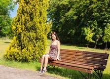 детеныши женщины парка стенда сидя Стоковые Фотографии RF