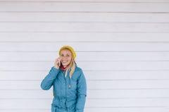 детеныши женщины телефона сь говоря женщина в желтом цвете связала шляпу и синий пиджак используя умный телефон Стоковое Фото