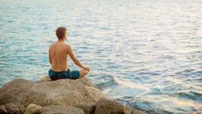 детеныши йоги человека практикуя Сидит в положении лотоса на береге океана видеоматериал