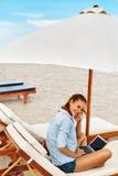 детеныши работы женщины официантки лета переднего ресторана стоящие Женщина ослабляя используя компьютер на пляже Независимое дел Стоковые Изображения RF