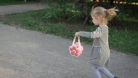 детство счастливое Милая маленькая блондинка, бега через парк, она носит striped платье акции видеоматериалы