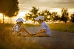 2 дет, братья мальчика, имеющ потеху outdoors с автомобилями игрушки Стоковое Изображение RF