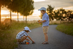 2 дет, братья мальчика, имеющ потеху outdoors с автомобилями игрушки Стоковые Фотографии RF