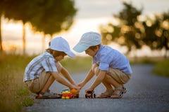 2 дет, братья мальчика, имеющ потеху outdoors с автомобилями игрушки Стоковые Фото
