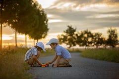 2 дет, братья мальчика, имеющ потеху outdoors с автомобилями игрушки Стоковая Фотография