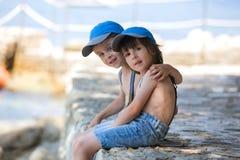 2 дет, братья мальчика, сидя на пристани на среднеземноморском s Стоковая Фотография