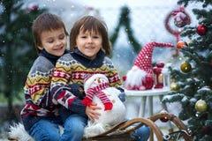 2 дет, братья мальчика, сидя на розвальнях рядом с christ Стоковая Фотография RF