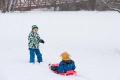 2 дет, братья мальчика, сползая с bob в снеге, wintertime Стоковая Фотография RF