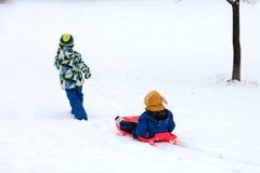2 дет, братья мальчика, сползая с bob в снеге, wintertime Стоковая Фотография