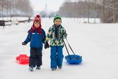 2 дет, братья мальчика, сползая с bob в снеге, wintertime Стоковое фото RF