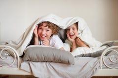 2 дет, брат и сестра, squirmy на кровати в спальне Стоковое фото RF