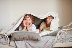 2 дет, брат и сестра, squirmy на кровати в спальне Стоковые Фото