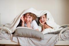 2 дет, брат и сестра, squirmy на кровати в спальне Стоковая Фотография