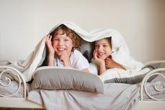 2 дет, брат и сестра, squirmy на кровати в спальне Стоковые Изображения