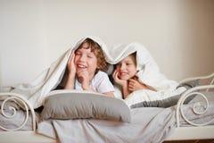 2 дет, брат и сестра, squirmy на кровати в спальне Стоковое Фото