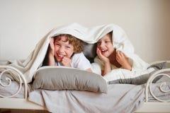 2 дет, брат и сестра, squirmy на кровати в спальне Стоковая Фотография RF