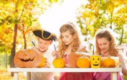 3 дет во время хеллоуина производя тыквы Стоковые Изображения RF