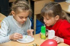 2 дет выпивают сок и едят торт на партии на школе Стоковые Изображения RF