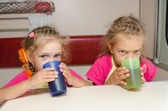 2 дет выпивают чай в поезде на таблице на более низком месте в второго класса фуре отсека Стоковое фото RF