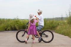2 дет в велосипеде летнего дня и мальчике и девушке цветка Стоковое Изображение