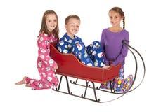 3 дет в пижамах зимы вокруг саней Стоковые Изображения RF