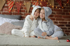 2 дет в пижамах сидя на подарках рождества кровати ждать Стоковое Фото
