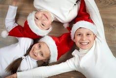3 дет в шляпах Санты лежа на деревянной предпосылке, имеющ потеху и счастливые эмоции, концепцию зимнего отдыха Стоковые Фото