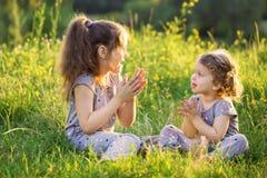 2 дет говоря и имея потеху на траве Стоковые Изображения