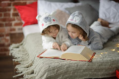 2 дет лежат на большой кровати и читают сказки Стоковые Изображения RF