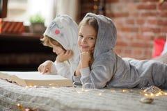2 дет лежат на большой кровати и читают сказы рождества Стоковые Изображения RF