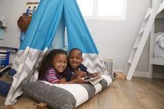 2 дет лежа в шатре в игровой с таблеткой цифров Стоковая Фотография RF