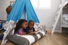 2 дет лежа в шатре в игровой с таблеткой цифров Стоковое Фото