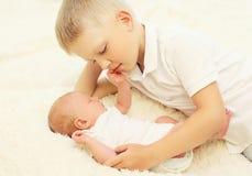2 дет лежа на кровати, самый старый обнимать брата самый молодой Стоковое Фото